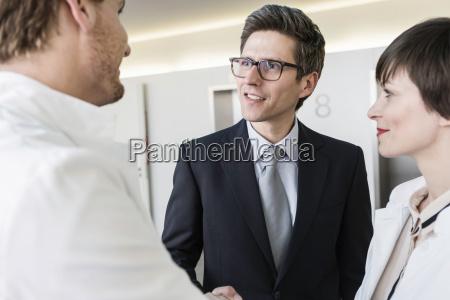 man wearing lab coat shaking hands