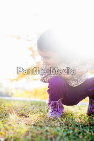 child squatting looking down at grass