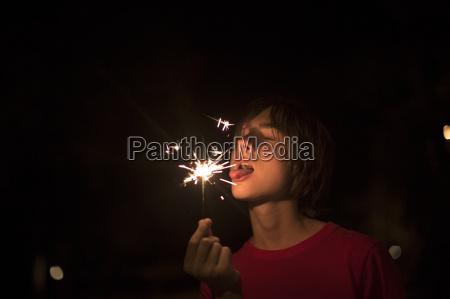 portrait of boy holding sparkler on