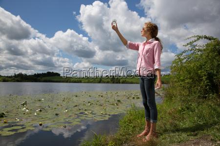teenage girl holding up glass jar