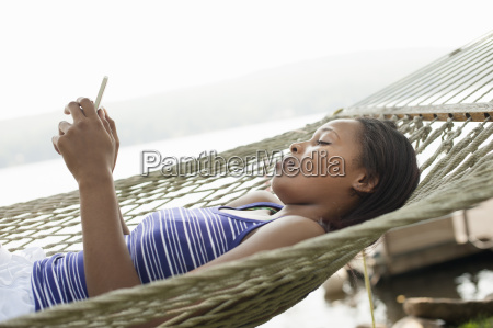 young woman lying in hammock using