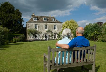 older couple sitting in backyard