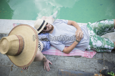 couple relaxing on blanket beside pool