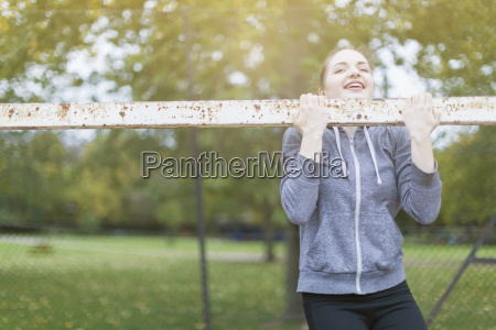 young woman doing chin up on
