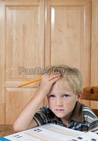 boy looking confused over homework portrait