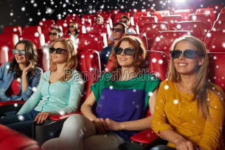 happy female friends watching movie in