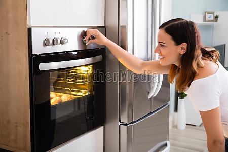 mujer usando horno de microondas en