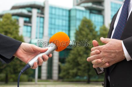 reportero sosteniendo microfono entrevistando empresario o