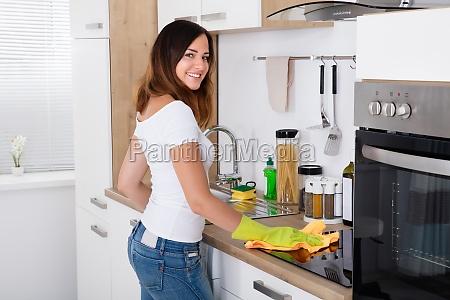 mujer feliz limpiando la cocina
