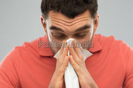 hombre enfermo soplando nariz a servilleta