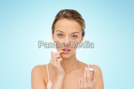 joven aplicando balsamo labial en sus
