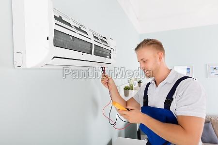 electricista verificando aire acondicionado