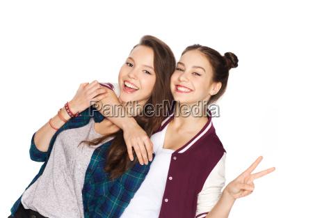 chicas adolescentes felices abrazandose y mostrando
