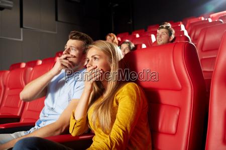 happy friends watching horror movie in
