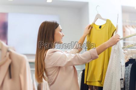 feliz joven mujer elegir la ropa