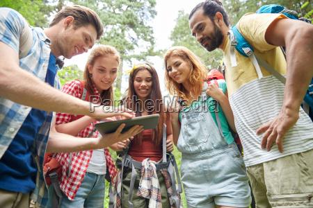 amigos felices con mochilas y tablet