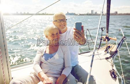personas mayores con smartphone tomando selfie