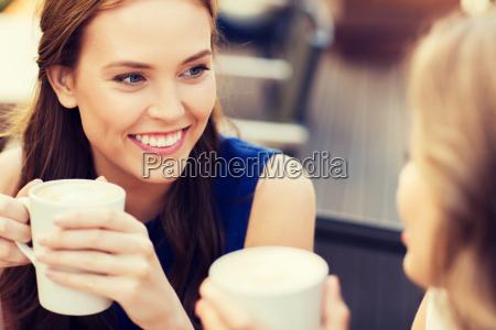 mujeres jovenes sonriendo con tazas de