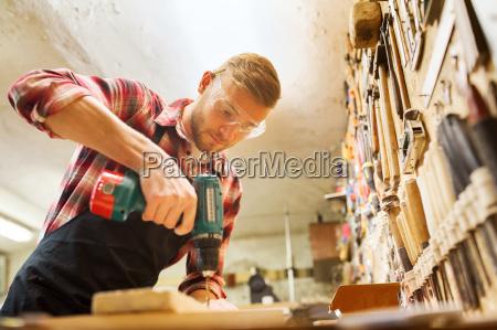 carpintero con el taladro que perfora