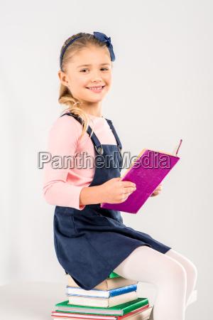 colegiala sonriente sosteniendo libro