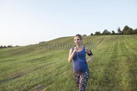 mujer embarazada corriendo en el campo
