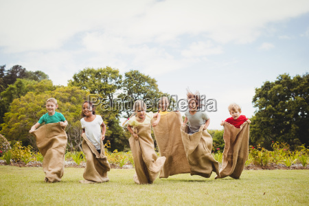 children having a sack race in