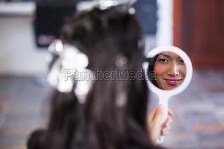 mujer mirando el espejo mientras espera