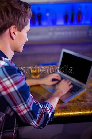 man using laptop on bar counter