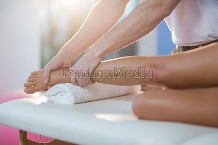 fisioterapeuta masculino dando masaje de rodilla