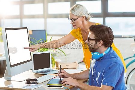 disenyadores graficos interactuan mientras trabajan en