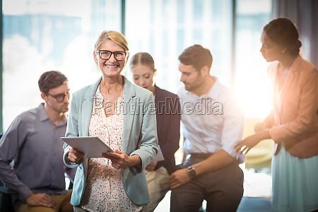 mujer empresaria sosteniendo tableta digital mientras