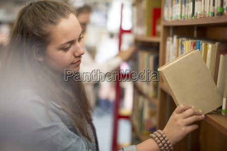 female student at the library putting