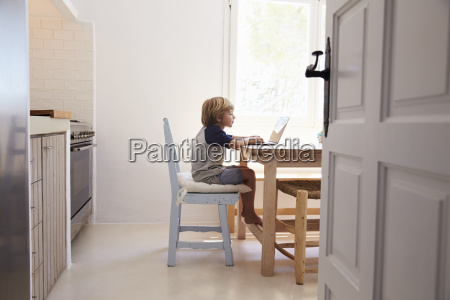 young boy using laptop in kitchen