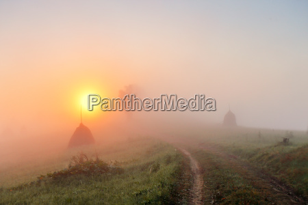 sunrise over mountain field haystacks and