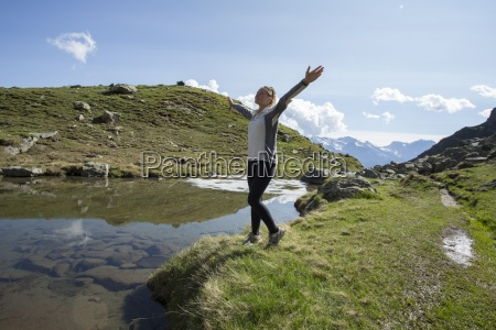 young woman celebrates at edge of