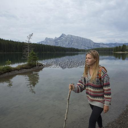 young woman hikes along mountain lake