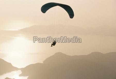 man paragliding over the mediterranean coast