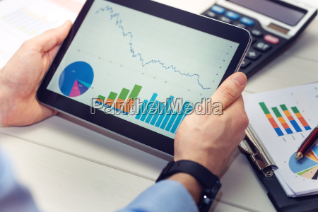 empresario sosteniendo tableta digital con graficos