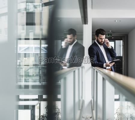 businessman standing in office building using