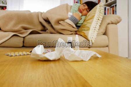 mujer enferma acostada en el sofa