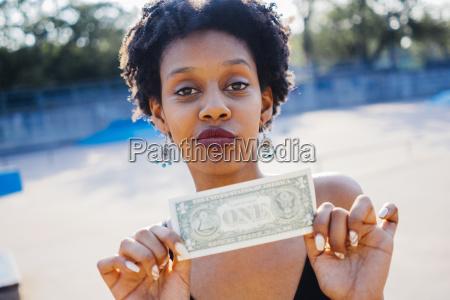 retrato de mujer mostrando un billete