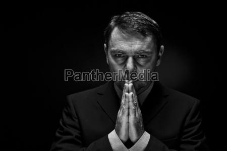 hombre maduro en traje completo orando