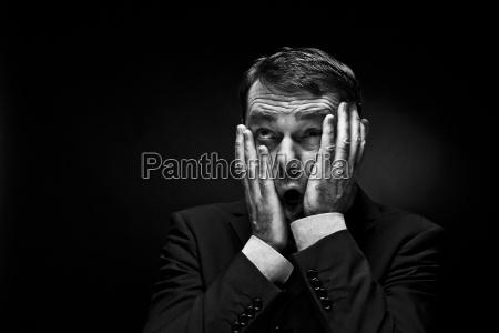 hombre maduro gestando contra fondo negro