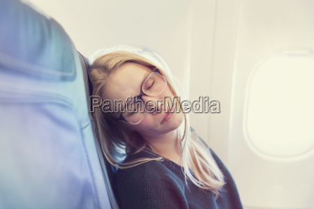 young woman sleeping in airplane