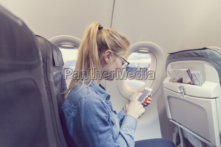blond young woman in airplane using