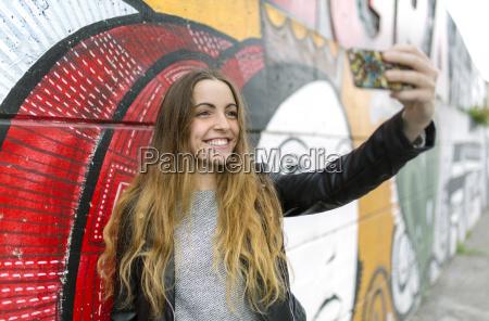 adolescente sonriente tomando un selfie en