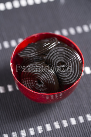 red bowl of liquorice wheels on