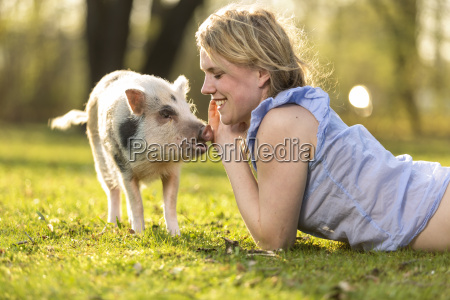 smiling woman lying with piglet in