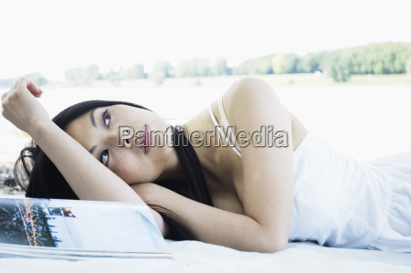 germany young woman lying with magazine