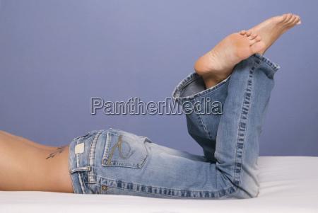 mujer en la cama con jeans